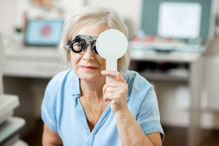 Senior woman with poor eyesight checking vision squinting her face during a medical examination at the ophthalmological office Stock Photo