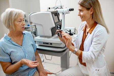 Augenarzt bietet einer älteren Patientin während einer medizinischen Beratung im Büro eine Brille für das Sehen an