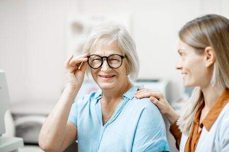 Happy senior woman patient checking vision with new eyeglasses during a medical consultation with ophthalmologist in the office