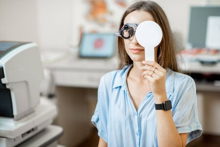 Young woman checking vision with eye test glasses during a medical examination at the ophthalmological office Stock Photo