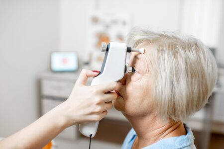 Doctor measuring the eye pressure with modern tonometer to a senior patient in the medical office, close-up