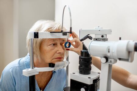 Senior woman during a medical eye examination with microscope in the ophthalmologic office Stock Photo