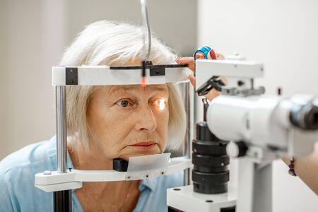 Starsza kobieta podczas medycznego badania wzroku pod mikroskopem w gabinecie okulistycznym