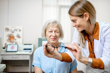 Ophthalmologist offering eyeglasses for vision to a senior woman patient during a medical consultation in the office 免版税图像