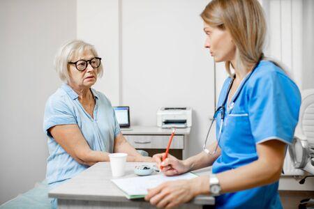 Krankenschwester, die während einer medizinischen Konsultation in der Klinik ein Rezept für die Krankengeschichte einer älteren Patientin schreibt