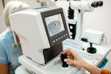 Augenarzt, der die Augen eines älteren Patienten mit einem digitalen Mikroskop während einer medizinischen Untersuchung untersucht, Nahaufnahme