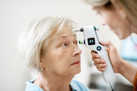 Female ophthalmologist measuring the eye pressure with modern tonometer to a senior patient in the medical office, close-up view Stockfoto