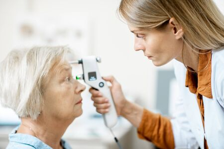 Female ophthalmologist measuring the eye pressure with modern tonometer to a senior patient in the medical office