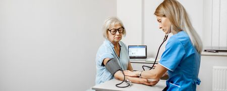 Nurse measuring blood pressure of a senior woman patient during an examination in the clinic. Senior care concept. Wide view with copy space