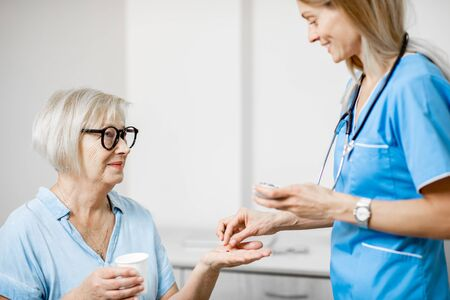 Nurse giving some medicine for a senior woman sitting on the couch, taking care of elder patients in the hospital Banque d'images - 133386601