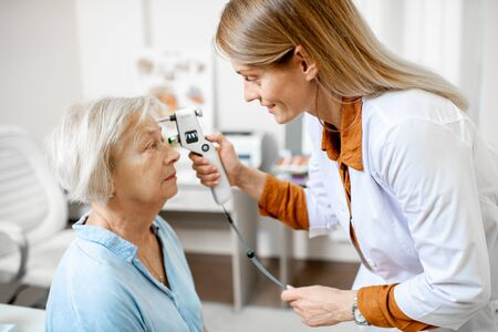 Augenärztin, die den Augendruck mit modernem Tonometer an einem älteren Patienten in der Arztpraxis misst
