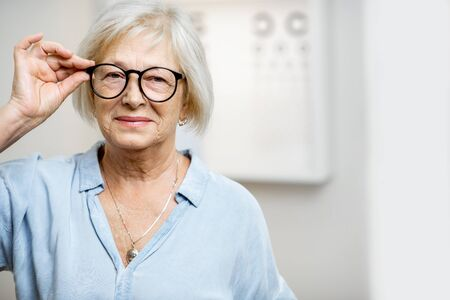 Portrait of a happy senior woman wearing eyeglasses in front of eye chart in ophthalmology office. Concept of checking eyesight and selecting glasses in older age Imagens
