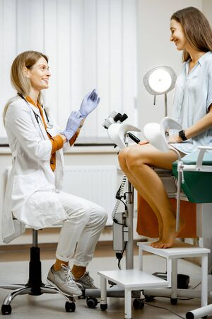 Gynecologist preparing for an examination procedure for a pregnant woman sitting on a gynecological chair in the office