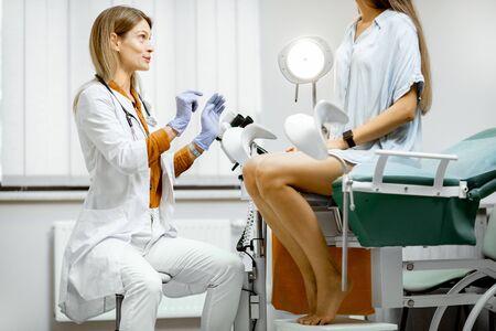 Ginecólogo preparándose para un procedimiento de examen para una mujer embarazada sentada en una silla ginecológica en la oficina Foto de archivo