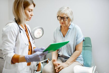 Senior woman sitting on the gynecological chair during a medical consultation with gynecologist. Concept of women's health during a menopause