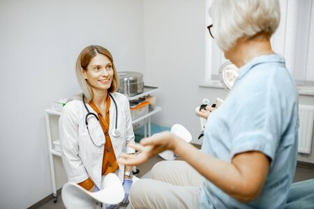 Gynecologist listening to a senior woman patient during a medical consultation in gynecological office. Concept of women's health during a menopause