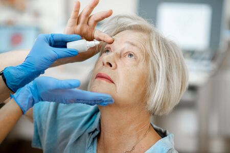 Doctor or nurse in medical gloves dripping eye drops on eyes of a senior patient during a treatment at the ophthalmological office, close-up view