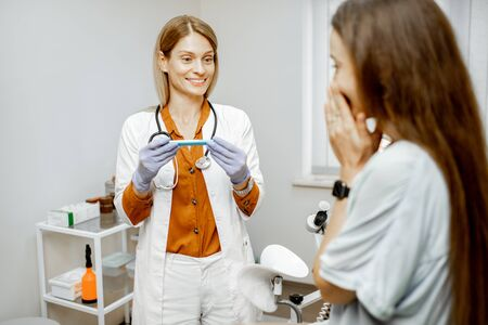 Gynecologist looking at pregnancy test during a medical examination with a young female patient feeling happy to know about pregnancy