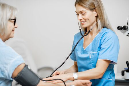 Nurse measuring blood pressure of a senior woman patient with tonometr during an examination in the clinic. Senior care concept