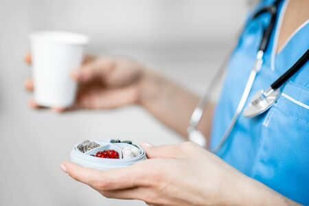 Nurse holding pillbox with medicine and a cup of water for the patient in the clinic, close-up view wit no face
