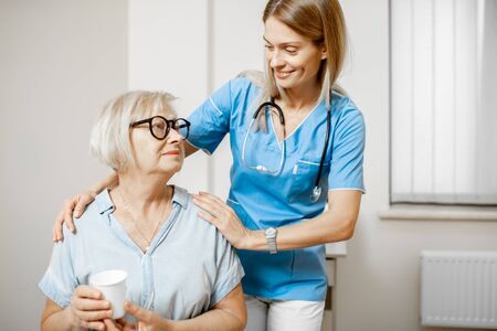 Nurse taking care of senior woman, hugging her shoulders in the clinic or home for elderly