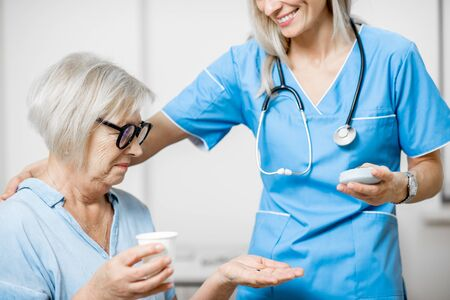 Nurse giving some medicine for a senior woman sitting on the couch, taking care of elder patients in the hospital Banque d'images - 133386693