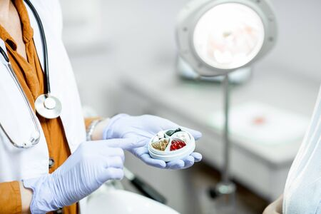 Doctor holding pillbox with some medicine in the gynecological office, close-up view on the hands and pills Zdjęcie Seryjne