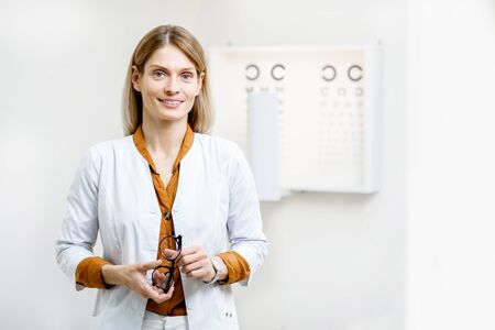 Portrait of a confident ophthalmologist in medical uniform standing in front of eye chart in the ophthalmological office. Vision test concept