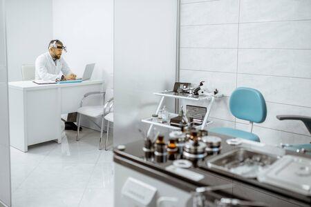 Oficina de otorrinolaringología con estación de trabajo ENT y médico senior que trabaja con una computadora portátil en el fondo