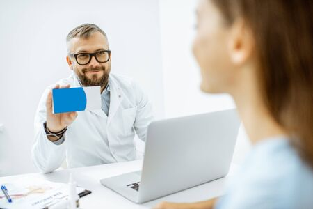 Senior doctor offering some medicine for a young patient, holding box with blank space to copy paste in the medical office