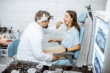 Patient avec oto-rhino-laryngologiste senior en cabinet ORL lors d'un examen médical, médecin examinant la gorge Banque d'images