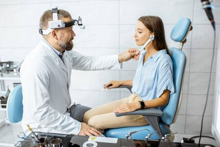 Senior otolaryngologist examining ears with ENT tuning fork for a young patient in the medical office. Hearing test with tuning fork concept Stock Photo