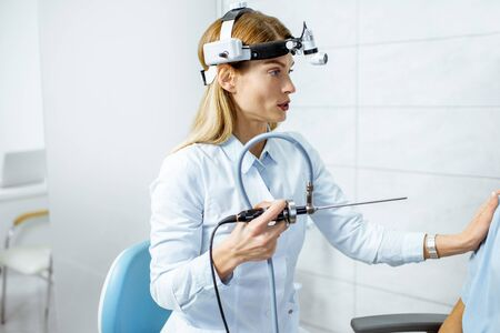 Portrait of a confident female otolaryngologist holding endoscope in the procedure room of the clinic