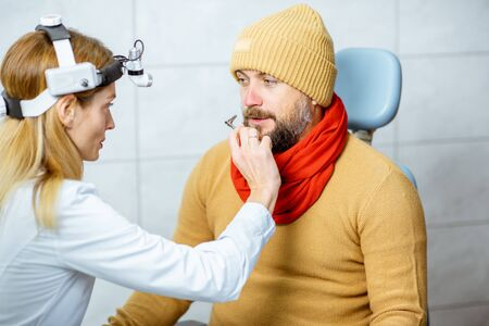 Adult patient catching cold, sitting in warm clothes with runny nose during a medical examination with otolaryngologist at the ENT office