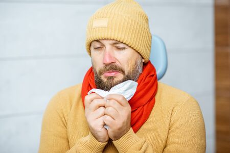 Portrait of an adult patient feeling sick, sitting in warm clothes with runny nose at the medical office