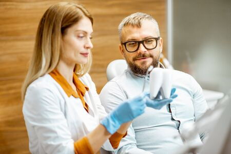 Female dentist and handsome man as a patient during a medical consultation at the dental office, doctor showing a tooth model Stok Fotoğraf