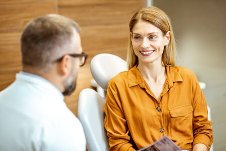 Beautiful adult woman as a patient with senior dentist during a medical consultation at the dental office
