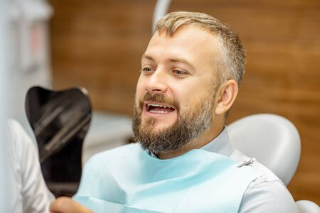 Man looking on the dental mirror, satisfied with his teeth, during a medical consultation at the dental office Stock Photo