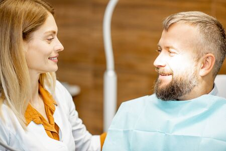 Female cheerful dentist and handsome man as a patient during a medical consultation at the dental office, smiling to each other Stock Photo