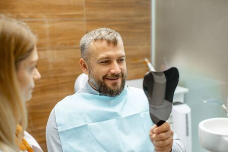 Man looking on the dental mirror, satisfied with his teeth, during a medical consultation with female dentist at the dental office Stock Photo