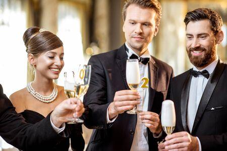 Grupo de personas elegantes bien vestidas con estilos retro celebrando las vacaciones de Año Nuevo, divirtiéndose con copas de vino en el salón del restaurante de lujo Foto de archivo