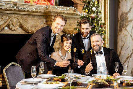 Portrait of an elegantly dressed people holding candles with 2021 numbers, celebrating New Year holiday at the luxury classical interior