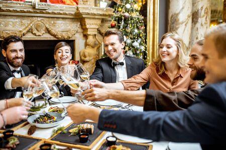 Gruppo di persone elegantemente vestite che si divertono, tintinnano bicchieri di vino durante una cena festiva vicino al camino e all'albero di Natale, celebrando le vacanze di Capodanno al ristorante di lusso