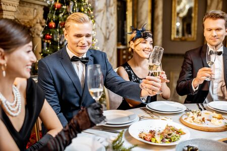 Elegantly dressed group of people having a festive dinner at a well-served table near the christmas tree, celebrating New Year holiday at the luxury restaurant