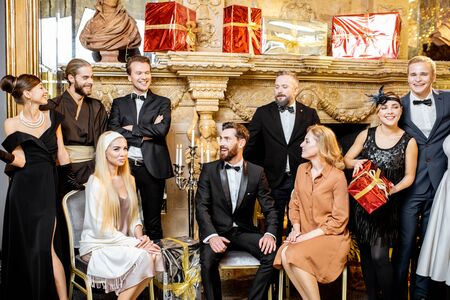Staged group photo of an elegant well-dressed people near the beautifully decorated fireplace with christmas tree and presents during a New Year celebration