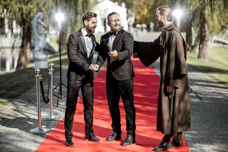 Portrait of a three men as well-known film actors during awards ceremony on the red carpet outdoors