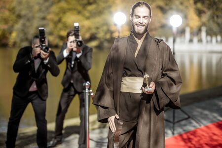 Man in costume as a well-known film character walking with annoying photo reporters on the red carpet during awards ceremony