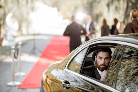 Portrait of a man as a famous movie actor sitting in the luxury car, arriving on the awards ceremony or movie premiere near the red carpet outdoors