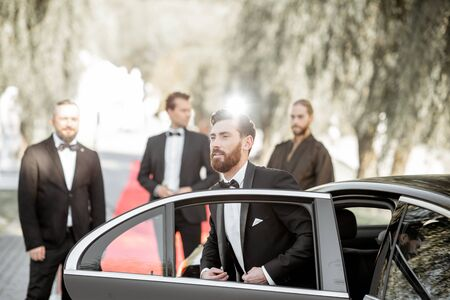 Man as a famous movie actor getting out the luxury car, arriving on the awards ceremony or movie premiere outdoors Foto de archivo - 133166406