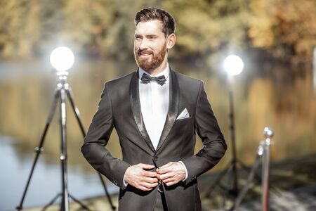 Portrait of an elegant man strictly dressed in tuxedo as a well-known actor during the awards ceremony outdoors